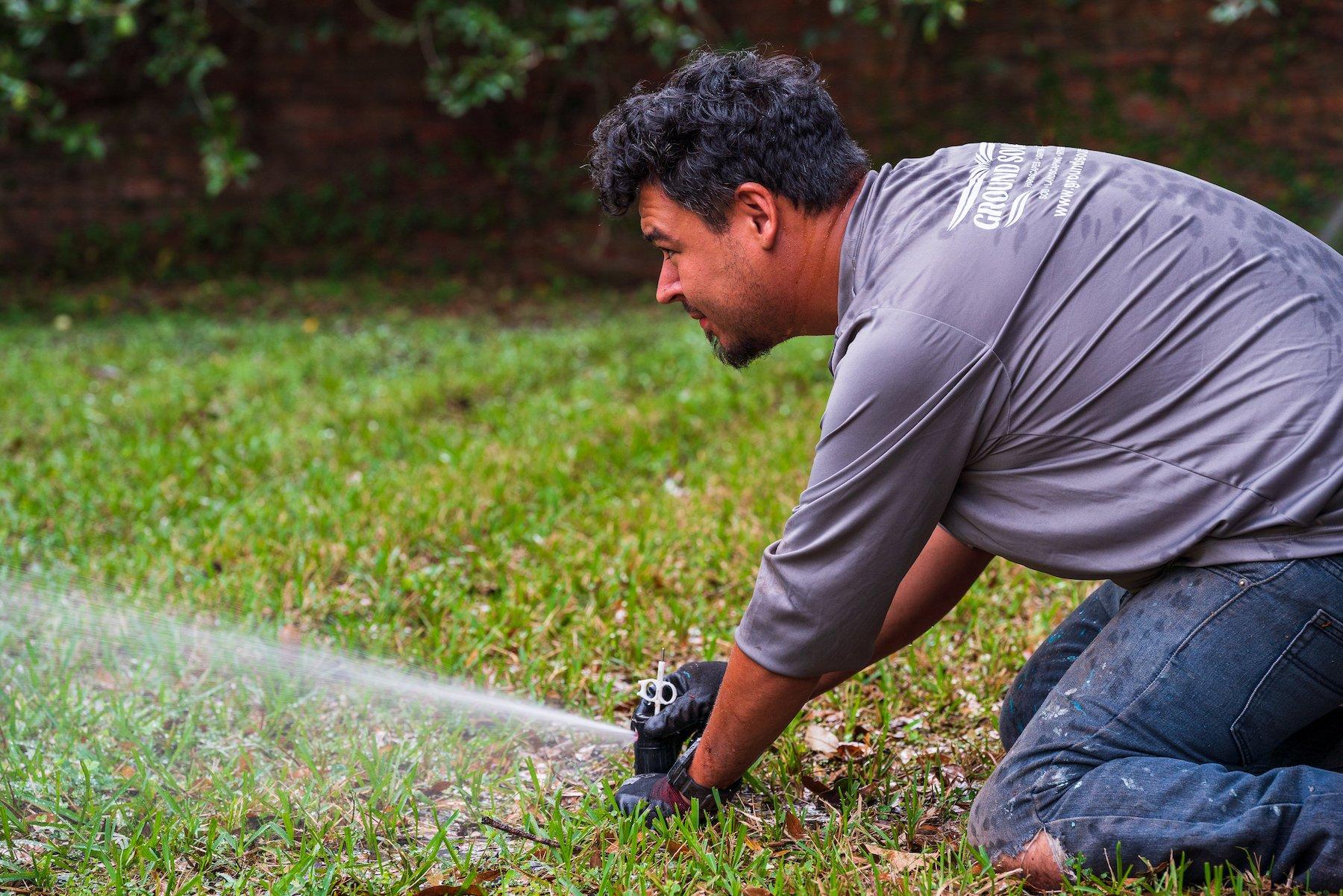 Landscape crew making an irrigation system adjustment