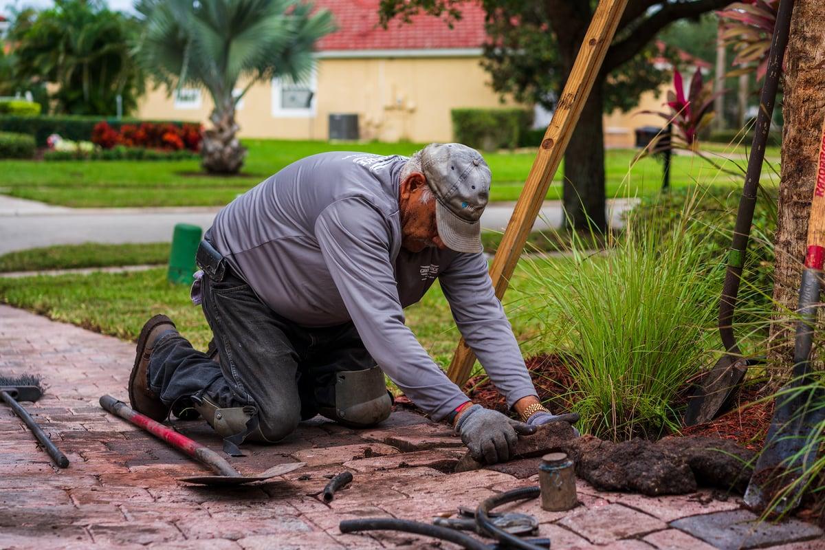 irrigation technician repairs sprinkler system