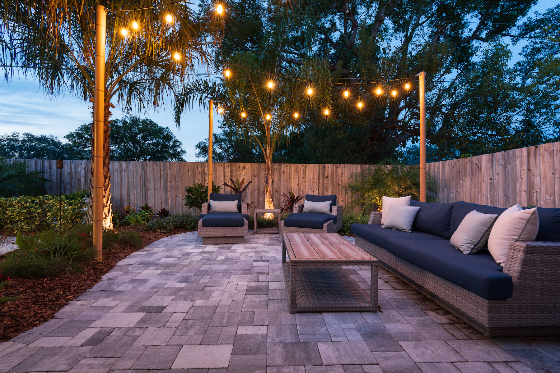 Lounging area with festive lights and paver patio