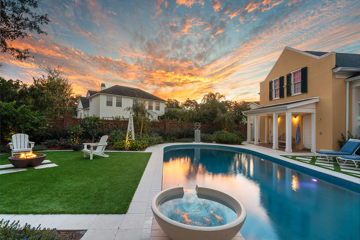 artificial grass around pool area with firepit and landscaping