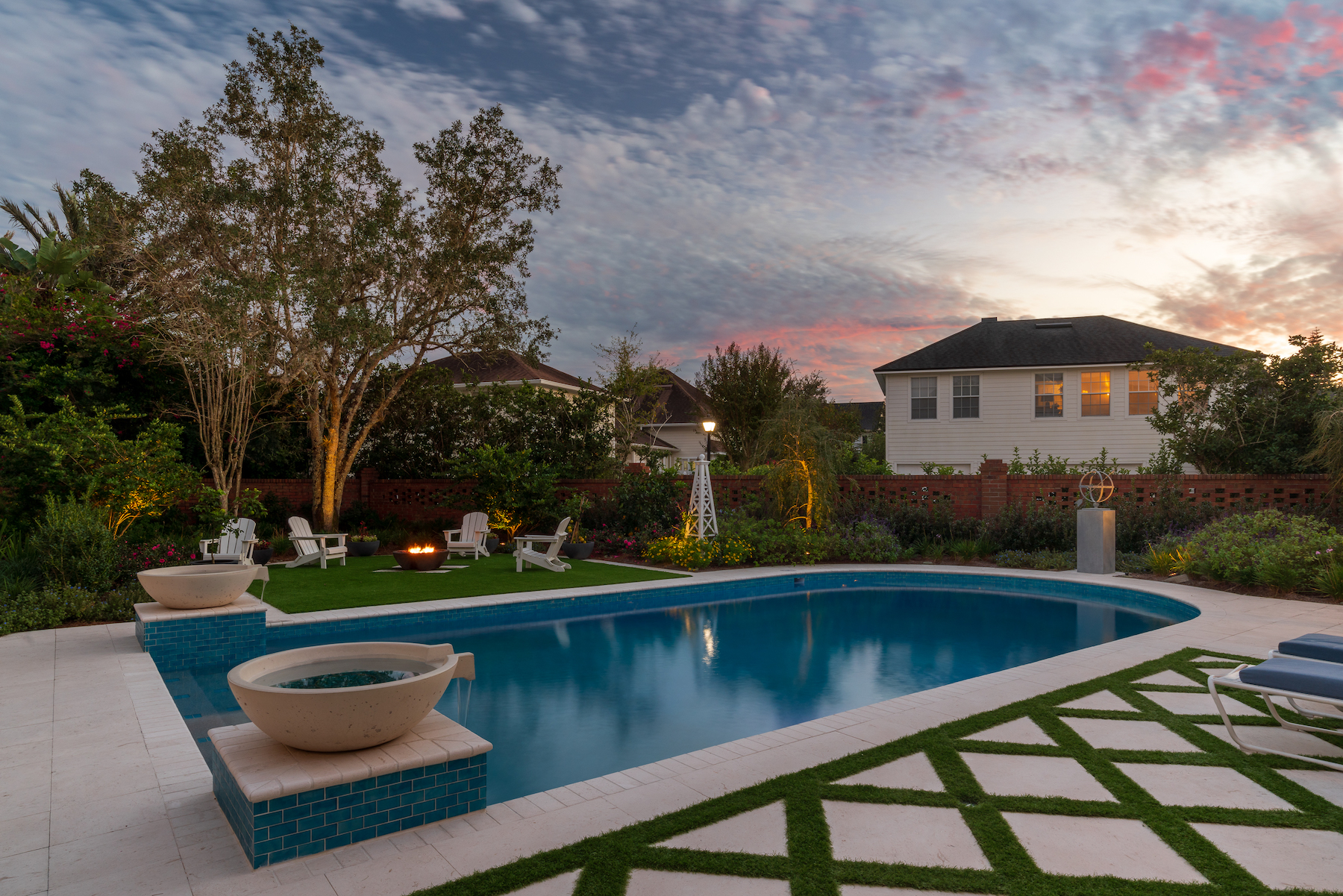 Poolside patio with white travertine and artificial turf
