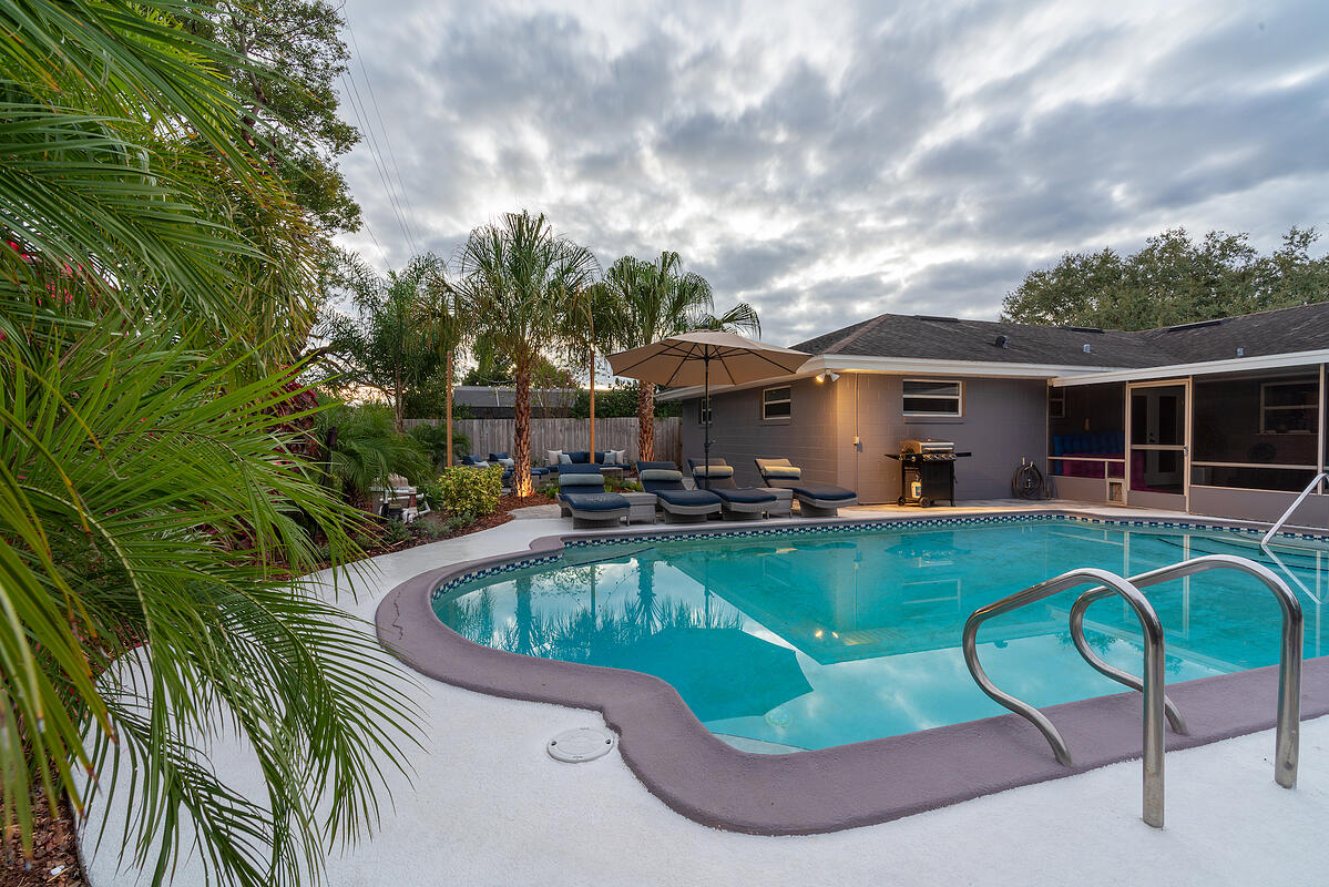 concrete around pool with landscaping and loungers