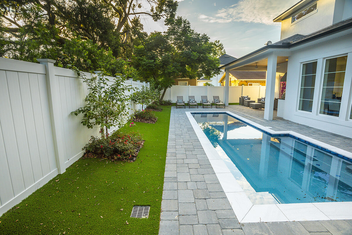 patio and artificial grass around pool