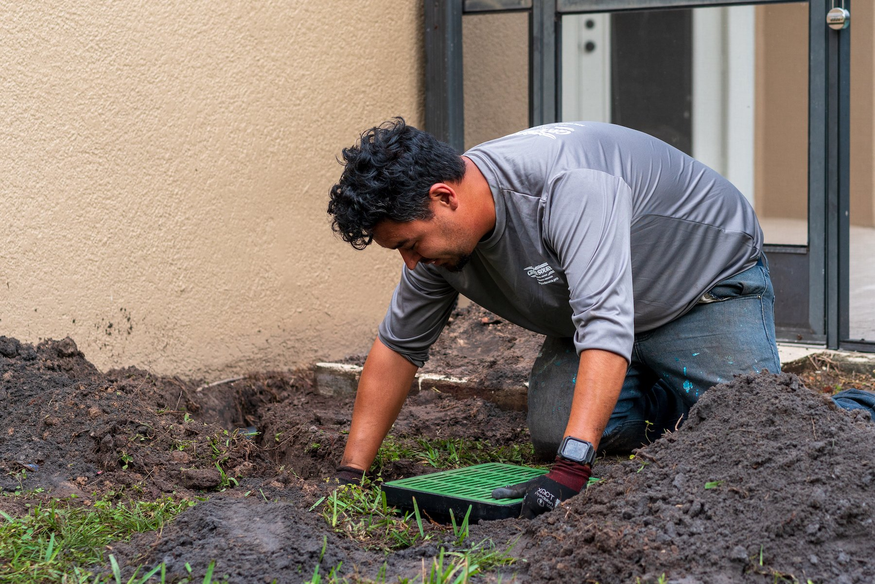 Landscape contractor installing drainage solutions for a yard